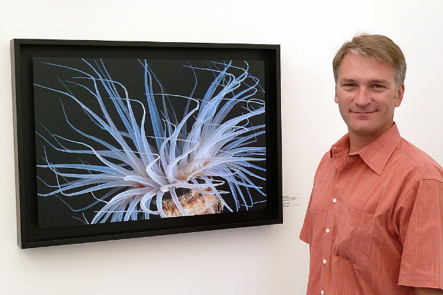photo of Derek Tarr at the San Diego Natural History Museum with his Tube Dwelling Anemone photo hanging in the 2010 Best of Nature Photography Show