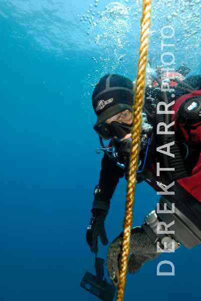 Scuba diver descending on anchor line