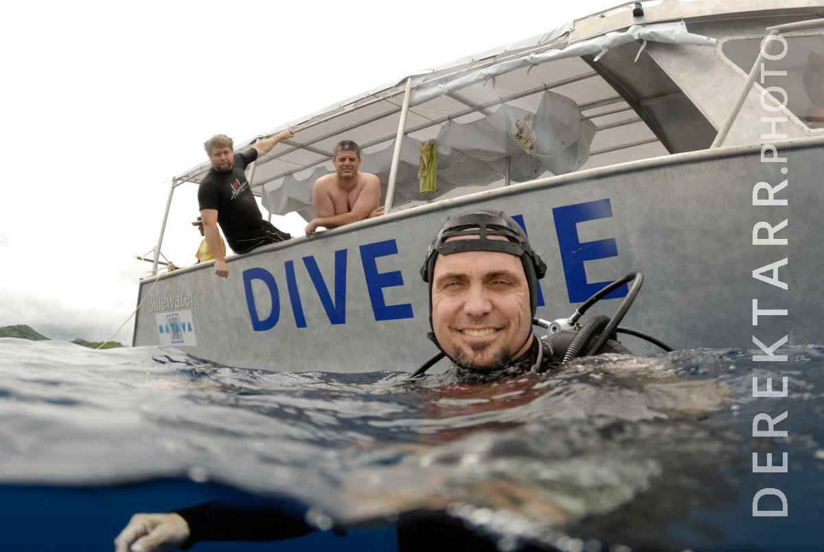large view of Scuba Diver in the Water Next to Dive Boat
