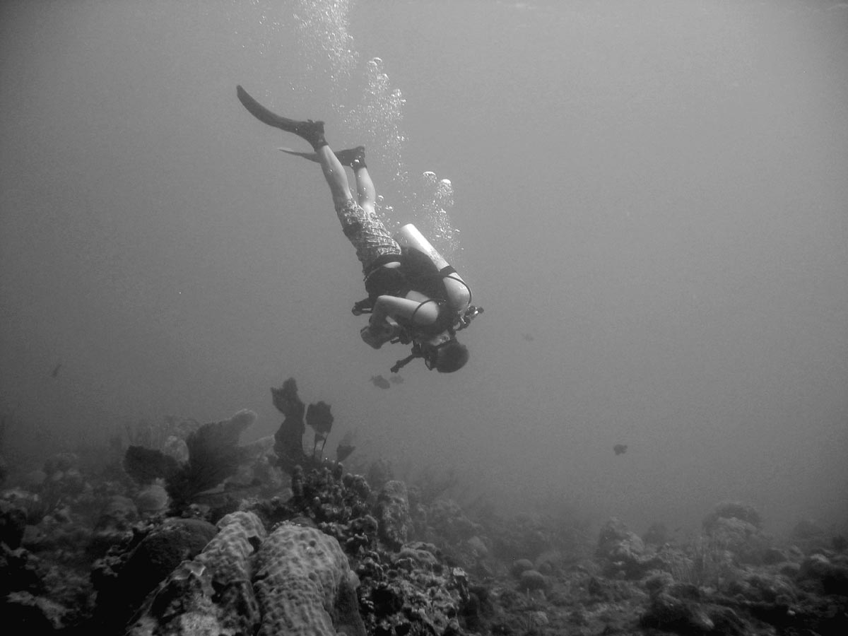 photo of Derek underater in board shorts and SCUBA gear hovering over the bottom in Grand Cayman